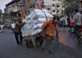 Labourers use a handcart to carry sacks at a wholesale grocery market in Delhi