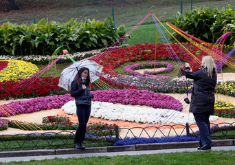 Woman with umbrella poses for a picture during visit to flower exhibition on rainy autumn day in Kiev