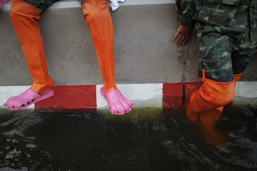 Thai soldiers helping commuters moving through flooded area wear protection from dirty water in Bangkok