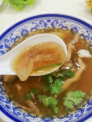 Braised Sea Cucumber in Brown Soup in in white spoon and beautiful blow