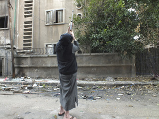 A man uses his rifle to hunt birds for food in the al-Khalidiya neighbourhood of Homs