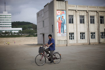 A local resident rides his bicycle next to a propaganda painting at the Special Economic Zone of Rason City