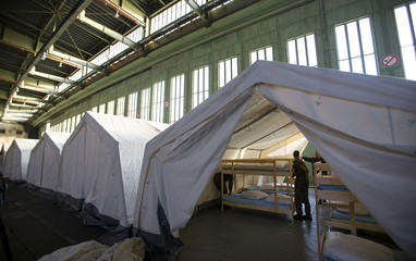 German armed forces Bundeswehr soldiers set up tents and beds for migrants in the hangar of the former Tempelhof Airport in Berlin