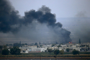 Smoke rise over the Syrian town of Kobani after fighting and explosions, as seen from the Mursitpinar crossing on the Turkish-Syrian border in the southeastern town of Suruc