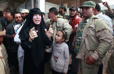 A woman reacts after seeing the corpse of Muammar Gaddafi in Misrata
