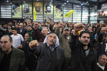 Hezbollah supporters react as they listen to their leader during a ceremony in Beirut