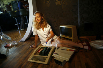 Model Laura poses with a historic computer during a photo shoot for the 'Nerd Dreams Calendar 2013' in Frankfurt