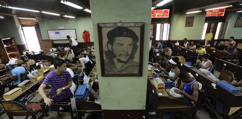 File photo of workers rolling cigars near a picture of Cuban revolutionary leader Che Guevara at the Partagas cigar factory in Havana