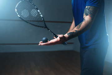 Male squash player training on indoor court