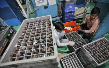 Employees pack auto components at the factory of the Samvardhana Motherson Group in Noida
