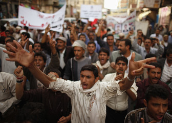 Protesters shout slogans during a protest march marking an attack by security forces on an anti-government protest camp in the southern city of Taiz last year, in Sanaa