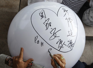 Poh writes his wishes within the shape of a heart on a wishing sphere in Singapore