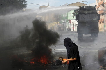 A masked student clash with riot police during a protest against the government to demand changes and end to the profiteering in the education system in Valparaiso