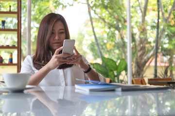 A beautiful Asian woman using smart phone with feeling relax in modern cafe