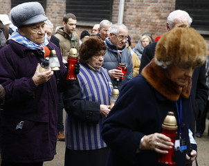 """Survivors walk to place candles at the """"death wall"""" in the former Nazi German concentration and extermination camp Auschwitz-Birkenau in Oswiecim"""