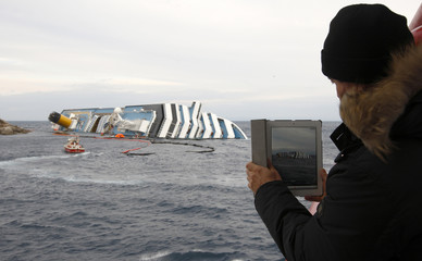 Man on a ferry uses an iPad to take a photo of the cruise liner Costa Concordia off the west coast of Italy at Giglio island