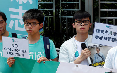 Oscar Lai and Joshua Wong from Demosisto, carrying a newspaper featuring a photo of bookseller Lam Wing-kee, protest outside China Liaison Office in Hong Kong