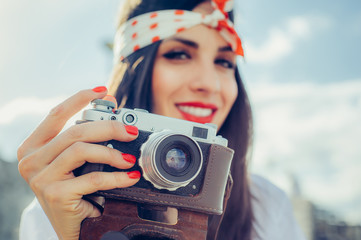 Beautiful woman taking photo with old fashioned film camera