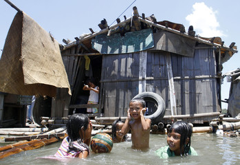 Children swim in murky waters to cool themselves off during a hot day outside their floating house along Manila Bay