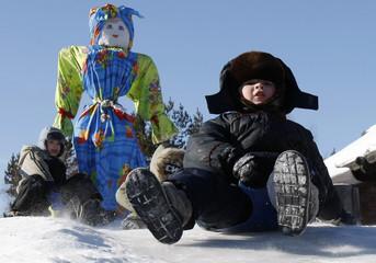 Children slide down a slope during a celebration for Maslenitsa, or Pancake Week, in Talcy settlement