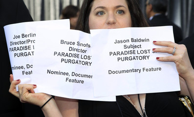 A publicist holds up signs identifying people arriving on the red carpet to help photographers identify them at the 84th Academy Awards in Hollywood
