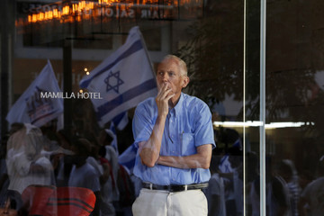 A man looks out from behind a glass wall of a hotel as an Israeli flag is reflected in the glass, in Jerusalem