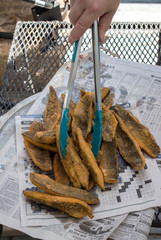 Fried Mullet stacked on newspaper at fish fry