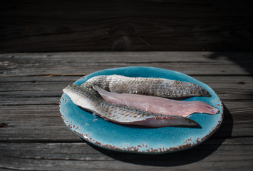 raw mullet fish fillets on blue plate at fish fry