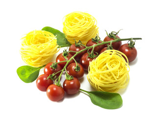 Cherry tomatoes with dry Italian pasta on a white background.