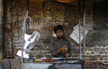 A man prepares meat to make kebabs at a roadside stall in New Delhi