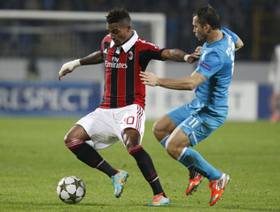Zenit St. Petersburg's Kerzhakov fights for the ball with AC Milan's Boateng during their Champion's league Group C soccer match in St. Petersburg's Petrovsky Stadium