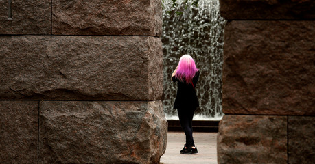 The hot pink hair of Haleyy Fischer from Louisville, KY, stands out against the dark stone as she takes a photo of a waterfall during a visit to the Franklin Delano Roosevelt Memorial in Washington
