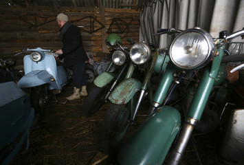 Collector Tsitovich, who finds and restores old cars and motorcycles, shows collection of motorcycles at his base in Zabroddzie