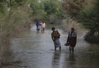 Villagers wade through floodwaters in Sommer Mallah