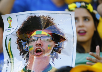 A Brazil fan places a picture of David Luiz over his face before the 2014 World Cup quarter-finals between Brazil and Colombia at the Castelao arena in Fortaleza