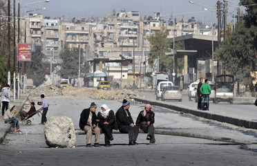 Men sit in the middle of the road in Aleppo