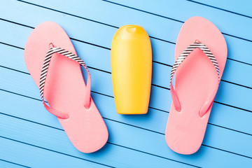 Pink flip flops on blue wooden table. Summer background