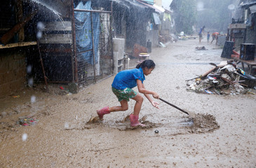 A resident removes mud on a street brought by monsoon rains in San Mateo
