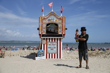 "Punch and Judy ""professor"" Mark Poulton poses for a photograph next to his booth at the seaside in Weymouth, southern England"