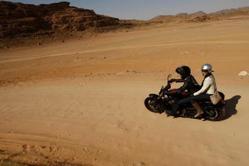A couple ride through the desert in Wadi Rum