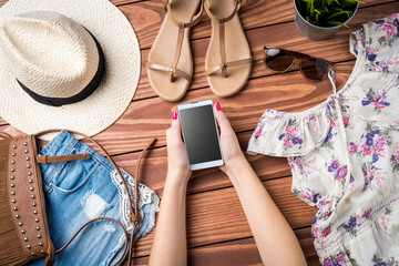 Women's summer clothes on wooden table. Fashion background
