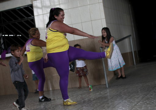 Hazel Castillo, takes part in an aerobics class next to her son Heiner Jaen, in Los Guidos de Desamparados