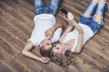 Man and woman young and beautiful couple in white shirts taking selfies on the wooden floor