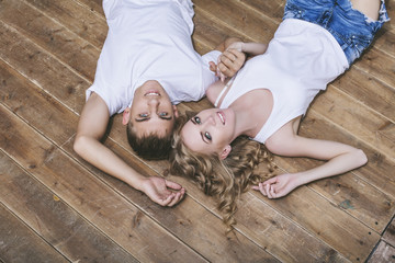 Man and woman young and beautiful couple in white shirts lying on the wooden floor