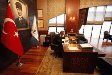 Turkey's PM Erdogan, with a portrait of modern Turkey's founder Ataturk in the background, works at his office at the AK Party headquarters in Ankara