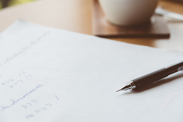 The black pencil is located on a paper that takes mathematics. And the coffee is gone in the coffee shop.