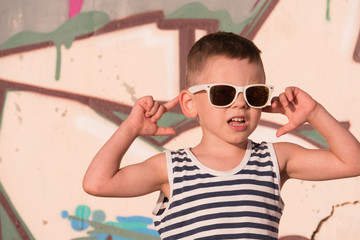 dreaming little kid wearing sunglasses and striped vest on graffiti background