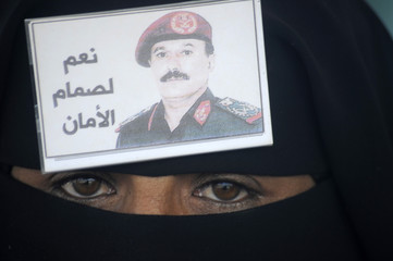 A woman wears a badge with an image of Yemen's President Ali Abdullah Saleh during a rally to show support for him in Sanaa