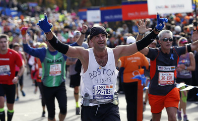 A runner raises his arms before crossing the finish line of the New York City Marathon