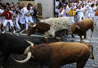 Runners sprint alongside Alcurrucen fighting bulls at the San Fermin festival in Pamplona